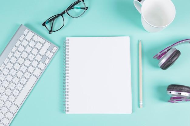 Bloc-notes à spirale vierge avec clavier; lunettes; tasse; casque et un crayon sur fond turquoise