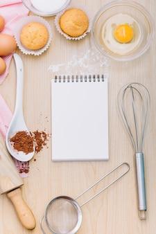 Bloc-notes à spirale vierge avec du jaune d'oeuf; petit gâteau; chocolat en poudre et outils sur le bureau en bois
