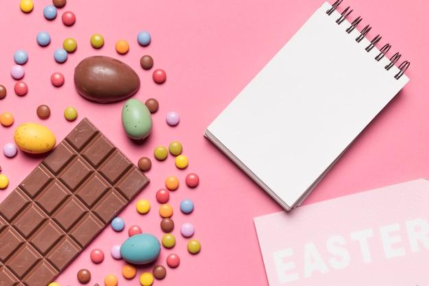 Bloc-notes en spirale vierge; mot de pâques; oeufs de pâques et bonbons multicolores sur fond rose
