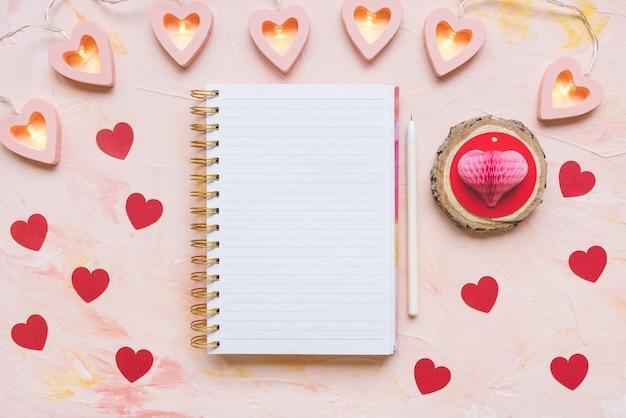 Bloc-notes, stylo et coeurs de papier rouge sur l'espace de travail de bureau. concept de la saint-valentin