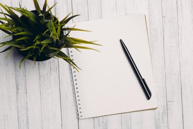 Bloc-notes avec stylo fleur en pot table en bois vue de dessus de bureau.