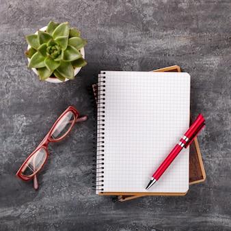 Bloc-notes avec stylo, lunettes et fleur. concept d'affaires