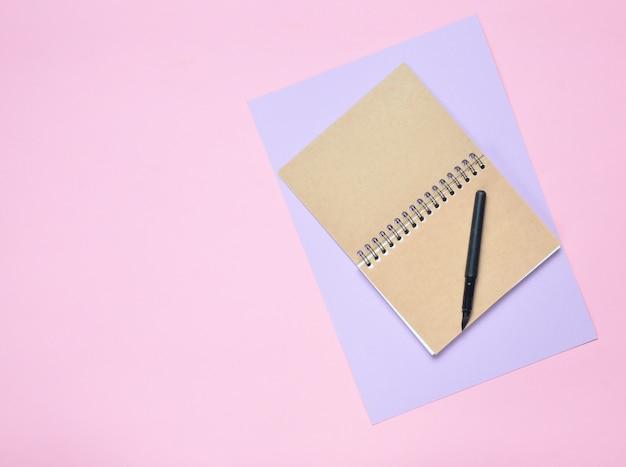 Bloc-notes avec stylo sur mur de papier de couleur. journal intime. vue de dessus.