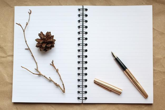 Bloc-notes, stylo en or et concert sur le bureau, table à cônes secs et branches décorées