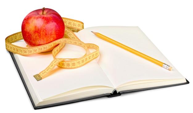 Bloc-notes et stylo avec pomme et ruban à mesurer pour écrire des notes diététiques - image isolée
