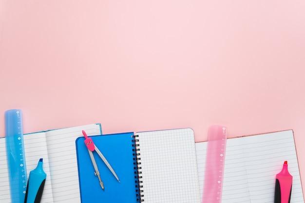Bloc-notes avec stylos, règle et boussole sur fond rose pastel. retour au concept de l'école. copiez l'espace pour votre texte