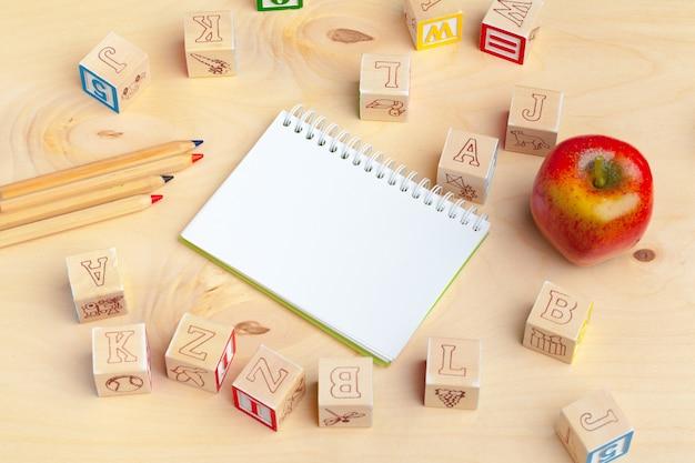 Bloc-notes sur table en bois et blocs d'alphabet en bois