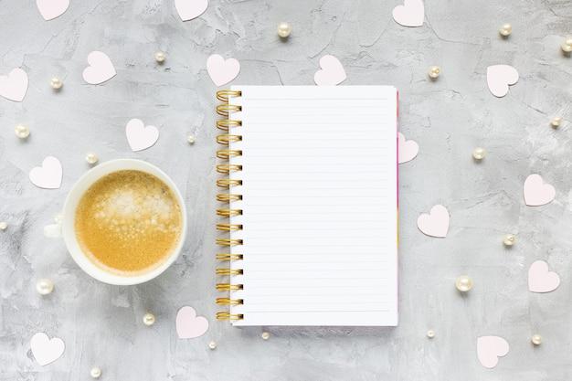 Bloc-notes, tasse de café et coeurs en papier rose