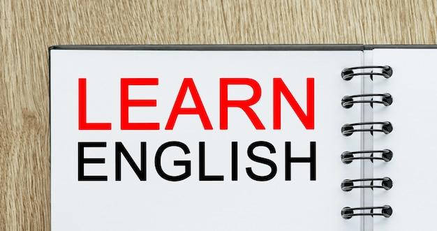 Bloc-notes avec texte apprendre l'anglais sur un bureau en bois. concept d'étude et d'éducation