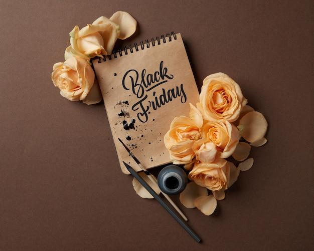 Bloc-notes avec un texte caligraphique et des fleurs sur une table marron, concept de vente black friday flat lay copy space