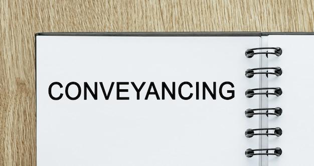Bloc-notes avec texte conveyancing sur un bureau en bois. concept commercial et financier