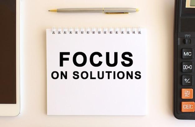 Bloc-notes avec texte focus on solutions sur fond blanc. concept d'entreprise.