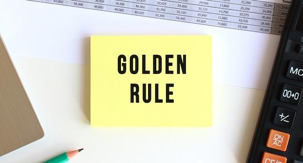 Bloc-notes avec le texte golden rule sur le bureau, près de l'ordinateur portable, de la calculatrice et des fournitures de bureau.