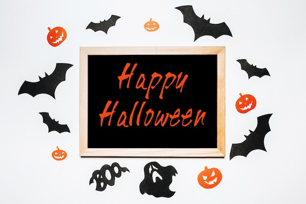 Bloc-notes avec texte happy halloween sur fond blanc et noir avec des chauves-souris, des citrouilles et des fantômes