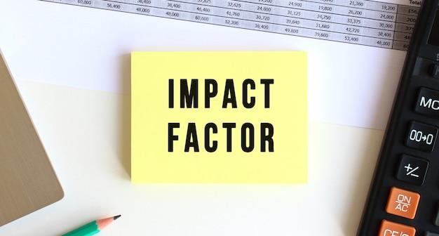 Bloc-notes avec le texte impact factor sur le bureau, près de l'ordinateur portable, calculatrice