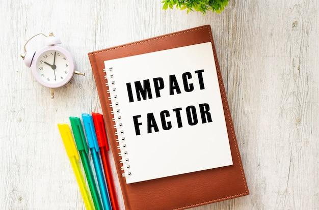 Bloc-notes avec le texte impact factor sur une table en bois agenda marron et stylos