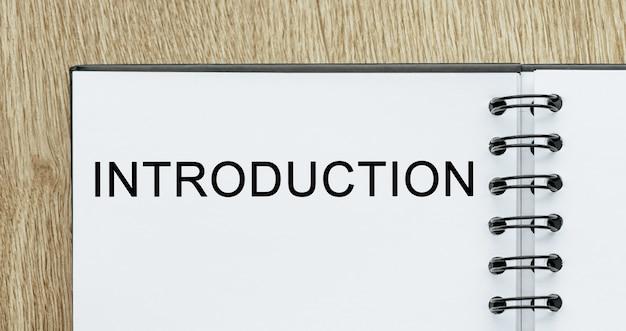 Bloc-notes avec texte introduction sur un bureau en bois. concept commercial et financier