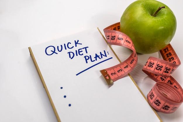 Le bloc-notes avec le texte de la liste plan de régime. concept de nutrition de régime de style de vie sain