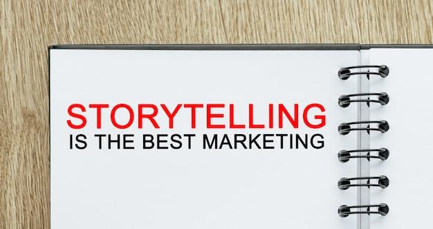 Bloc-notes avec texte la narration est le meilleur marketing sur un bureau en bois. concept commercial et financier