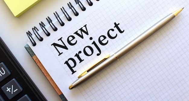 Bloc-notes avec texte nouveau projet, à côté se trouve une calculatrice et des papiers jaunes.
