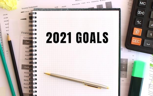 Bloc-notes avec texte objectifs 2021 sur le bureau, près des fournitures de bureau