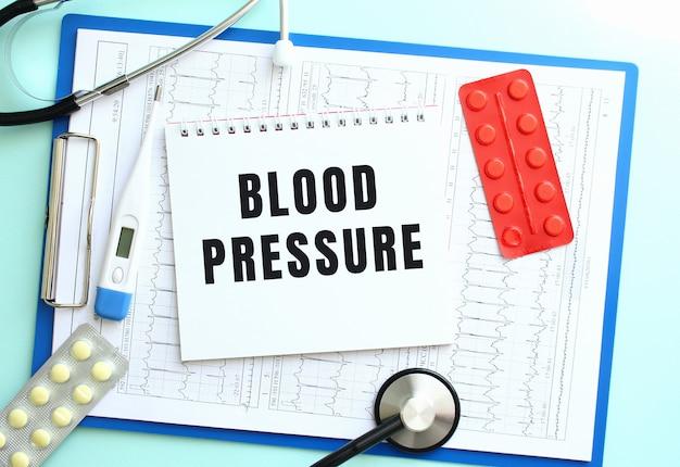 Un bloc-notes avec le texte pression artérielle se trouve sur un presse-papiers médical avec un stéthoscope et des pilules sur fond bleu.