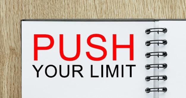 Bloc-notes avec texte push your limit sur un bureau en bois. concept commercial et financier