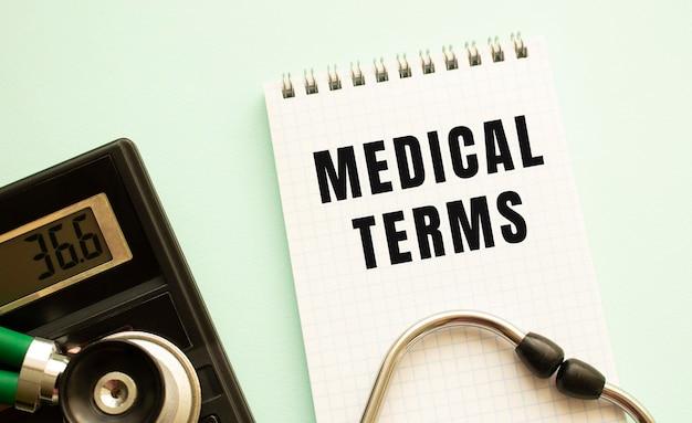 Bloc-notes avec texte termes médicaux, calculatrice et stéthoscope sur fond blanc. concept médical.