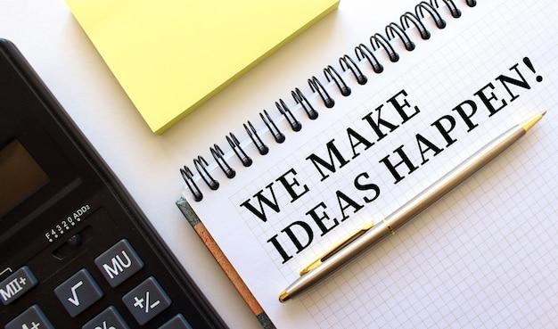Bloc-notes avec texte we make ideas happen, à côté se trouve une calculatrice et des papiers jaunes.