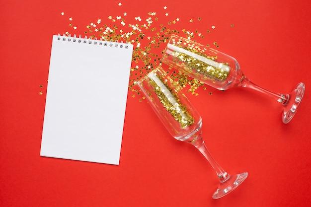 Bloc-notes et verres de champagne avec des confettis d'étoiles d'or, concept de noël et du nouvel an