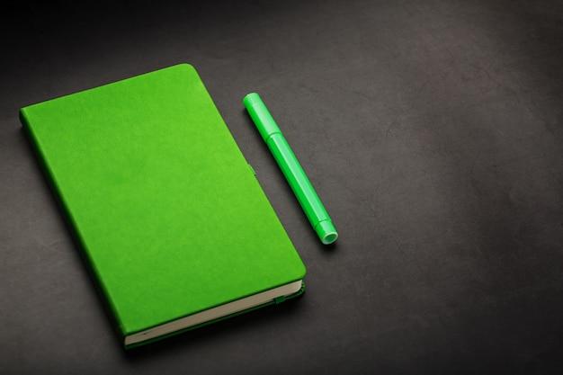 Bloc-notes vert avec une vue de dessus du stylo-feutre.