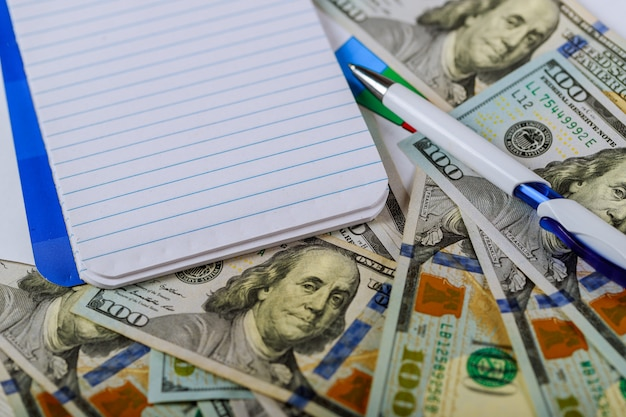 Bloc-notes vide sur les billets en dollars avec un stylo