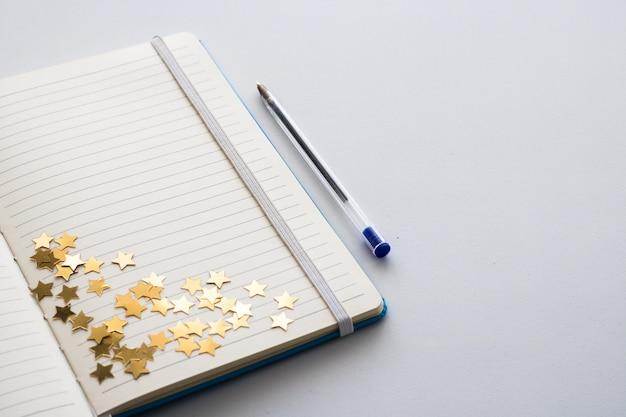 Bloc-notes vide avec des étoiles scintillantes. espace pour le texte.