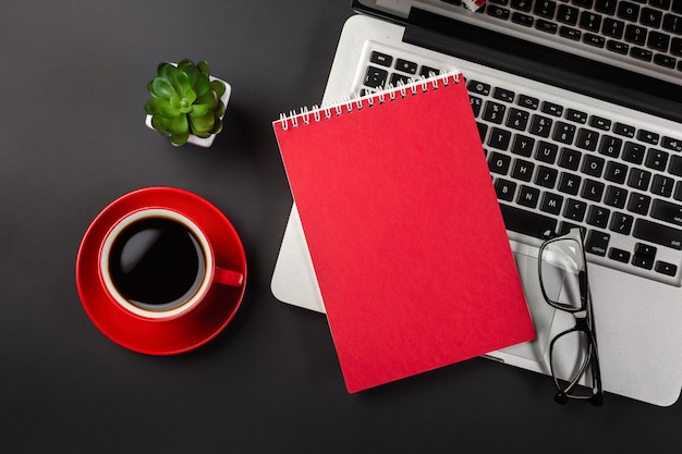 Bloc-notes vide sur un ordinateur portable et une tasse de café sur une table de bureau noire