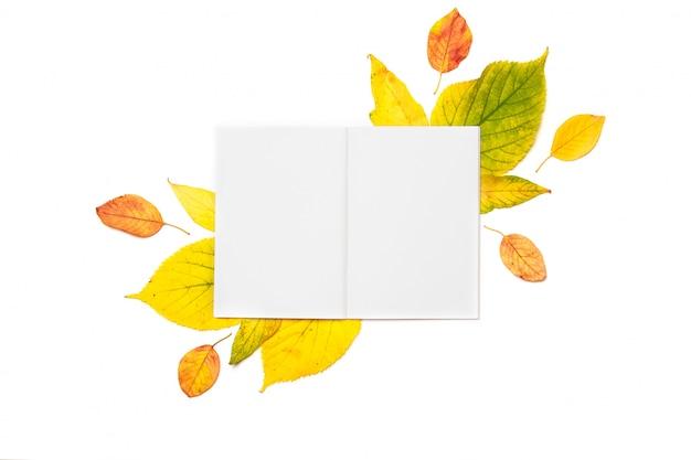 Bloc-notes vide pour écrire sur un automne de feuilles colorées, isolé sur blanc.