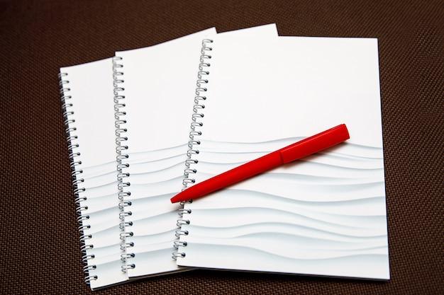 Bloc-notes vide pour le texte avec un stylo rouge sur fond en bois.