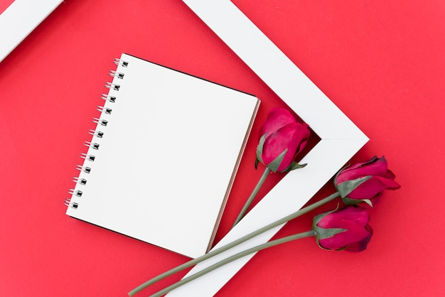 Bloc-notes vide avec des roses rouges dans le cadre