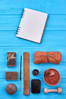 Bloc-notes vierge avec accessoires de bain spa aromatique sur bois. fond de bureau bleu tir vertical.