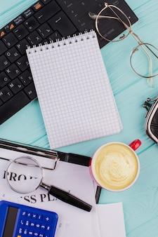 Bloc-notes vierge sur clavier et tasse de café sur un bureau bleu clair. diverses fournitures de bureau se composent d'un presse-papiers loupe calculatrice.