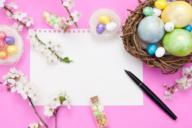 Bloc-notes vierge et feuille de rucca avec des éléments décoratifs de pâques. maquette de printemps pour vos textes