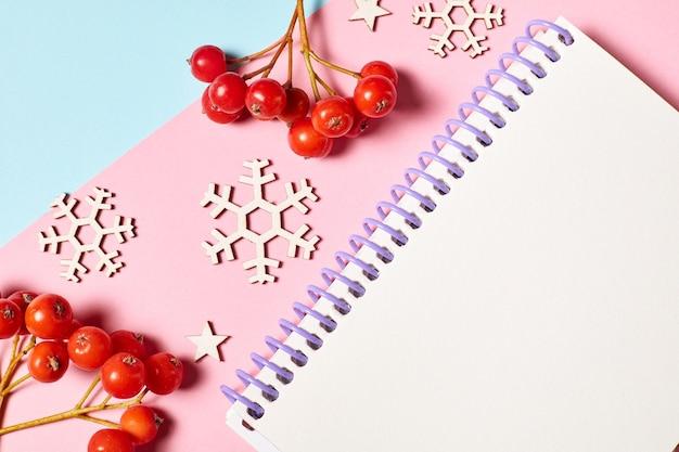 Bloc-notes vierge sur fond bleu rose décoré de baies de sorbier et de flocons de neige