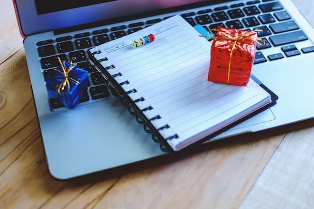 Bloc-notes vierge avec liste de lettres de lettres et boîtes-cadeaux sur ordinateur portable