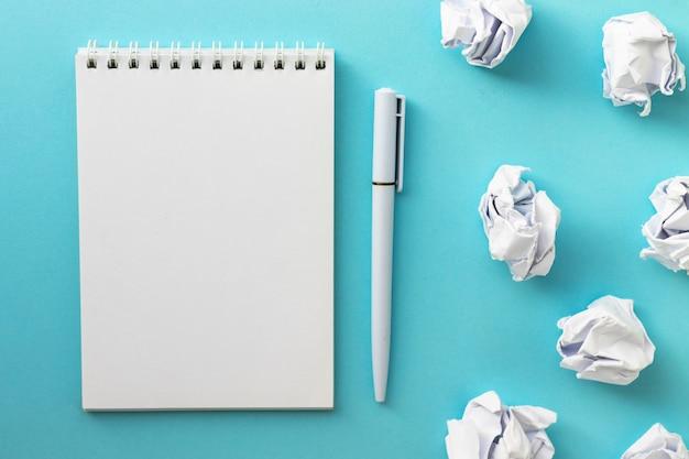 Bloc-notes vierge, stylo et boules de papier froissé sur jaune. rédaction d'un message. nouvelle ou mauvaise idée. mise à plat.
