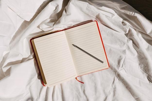 Bloc-notes vierge avec un stylo sur le lit