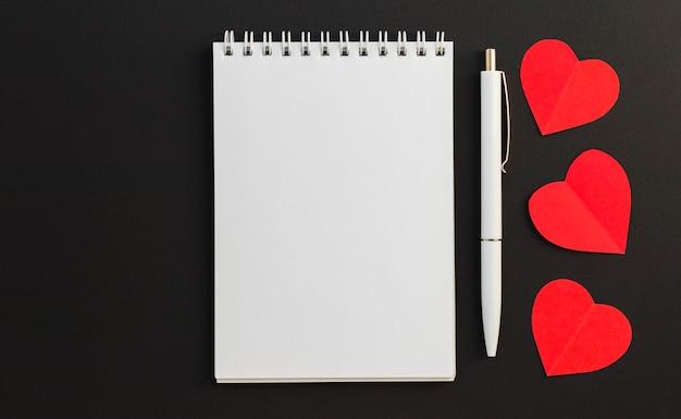 Bloc-notes vierge, stylo et trois coeurs de papier rouge sur fond noir. message d'amour. saint-valentin et concept de vacances romantiques. vue de dessus, mise à plat avec espace de copie.