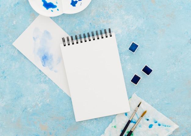 Bloc-notes vue de dessus avec des pinceaux sur la table