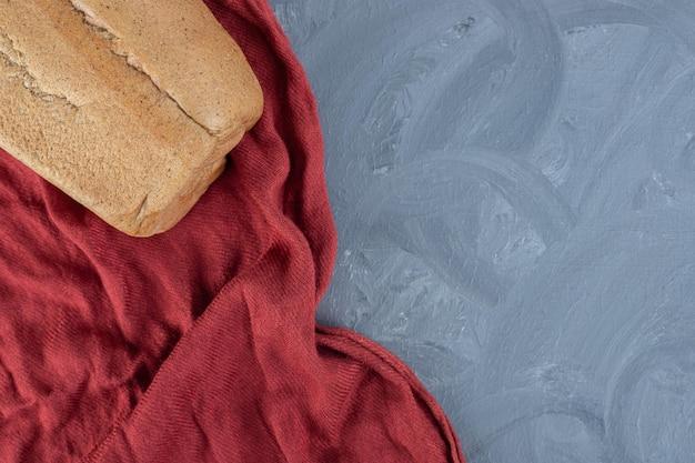 Bloc de pain sur nappe rouge froissé sur table en marbre.