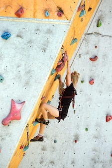 Bloc, petite fille grimpant au mur et grimpeur aux poignées multicolores. activité de loisir
