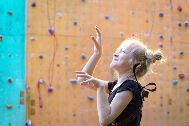 Bloc, petite fille s'amuser sur le fond du mur d'escalade