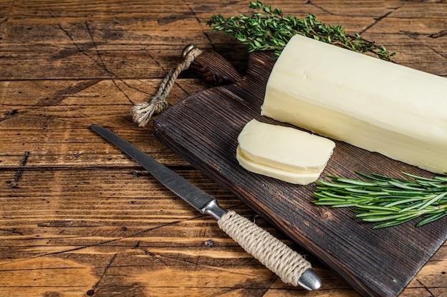 Bloc à tartiner en tranches de beurre sur une planche de bois avec des herbes. fond en bois. vue de dessus. espace de copie.